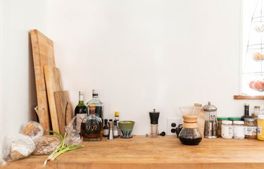 food, spices, and cutting boards on a wooden countertop