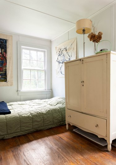a large off-white vintage armoire towers over a low bed with no frame