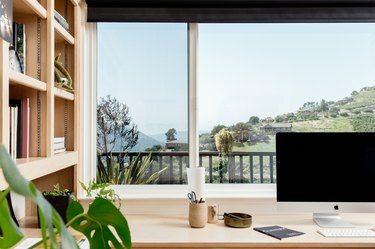 A light wood desk with a computer and containers. A bookcase is beside. A window view overlooking hills and neighboring homes.