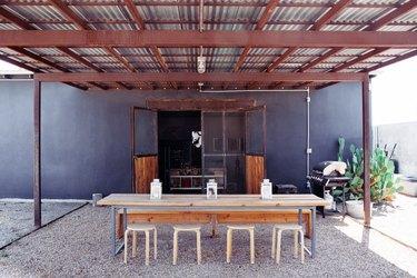 industrial farmhouse table, metal stools, wood bench, metal pergola, gravel.