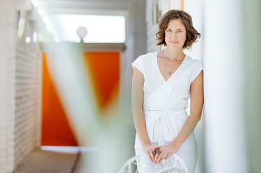 a woman in white leans on a white wall and holds a white chair