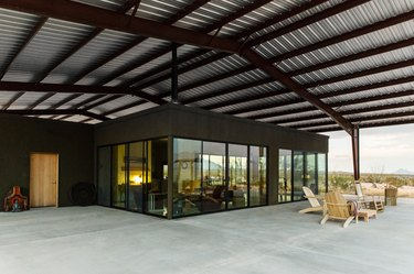 rustic industrial decor with corrugated metal and wood pergola over concrete patio with wood furniture.