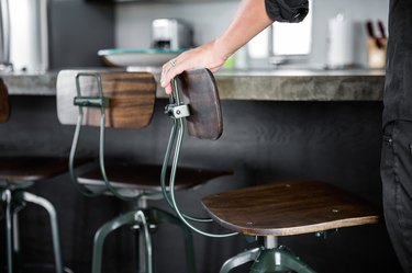 rustic industrial decor with wood and metal schoolhouse style barstools, dark finish bar.