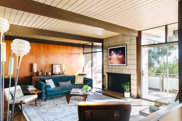 Midcentury living room with paneled walls and large white cinder block fireplace