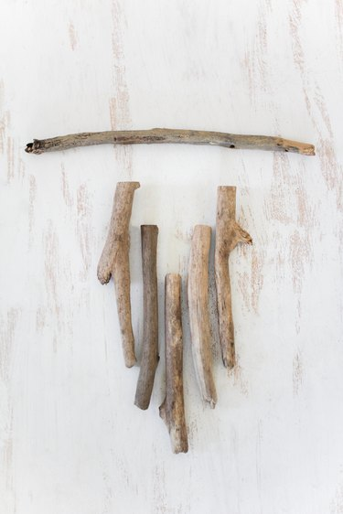 a diy wall hanging project in progress with sticks lined up as they will appear in the final product