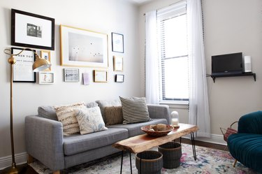Gray living room sofa with pillows, a rustic wood table and an art wall