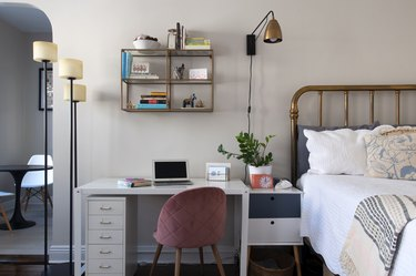 A bedroom with an office desk and a pink velvet chair