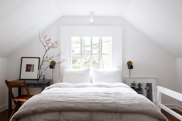 Bedroom with white walls and bedding with slanted ceiling and farmhouse furniture