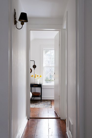 Hallway Lighting Ideas in Wood floor hallway with white walls and lamp wall sconce leading to bedroom