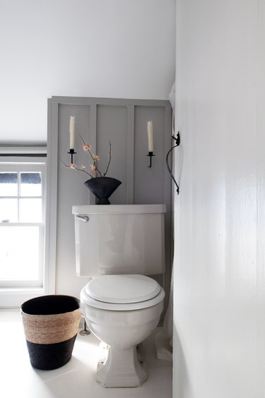 White and gray walled bathroom with candle sconces and vase with plantToilet in bathroom.