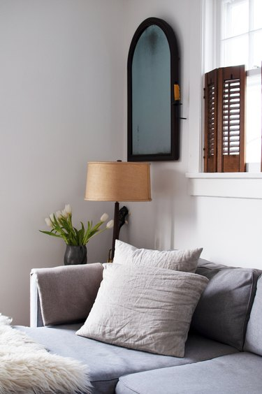 Gray sofa in white walled living room with brown shutter windows