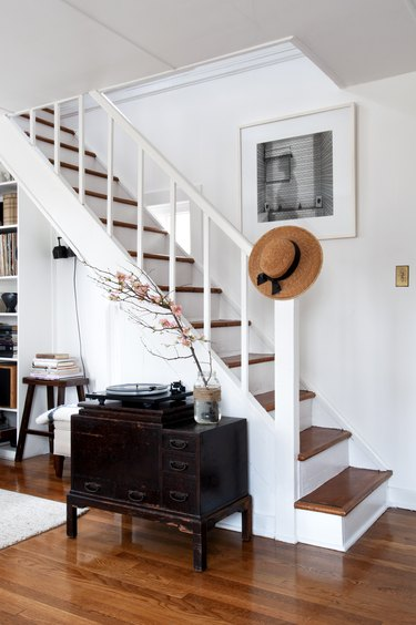 White staircase with wood flooring and farmhouse style furniture