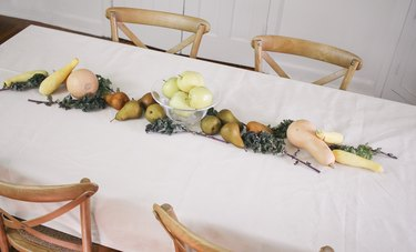 large fruits and vegetables such as melons, squash, and pears form an edible  table runner