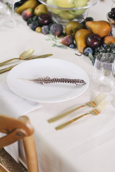 a table with a runner made of fruits and vegetables, gold cultery, and white plates with a single turkey feather on each one