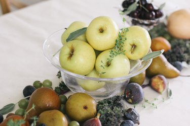 a clear bowl of apples forms the centerpiece for a table with an edible runner