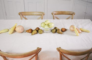 large fruits and vegetables such as squash and pears form the base of an edible table runner