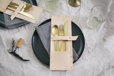 a leather flatware pocket holding gold utensils on a black plate