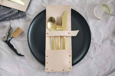 a leather flatware pocket holding gold utensils on a black plate
