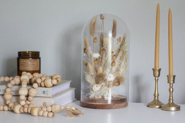 Cloche with dried plants and candlesticks with wood bead necklace