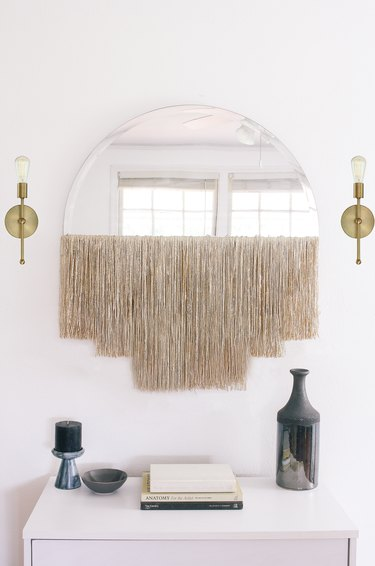 Round mirror with fringe beside gold sconces over white dresser with vase