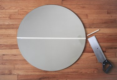 Round mirror with saw and cut wood dowel