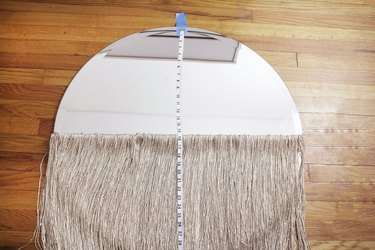 Round mirror with neutral curtain fringe and measuring tape