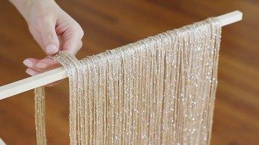 Hand placing neutral fringe curtain panels on wood dowel