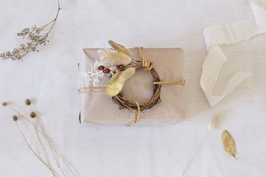 Package wrapped in neutral paper with dried plants and twigs