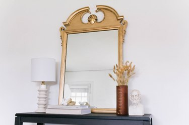 Gold antique style mirror on black side table with lamp, books, vase of dried plants, sculpture bust