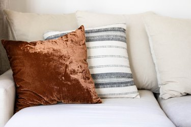 brown velvet pillow with striped neutral pillow on grey couch