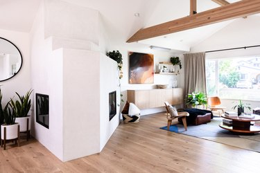 wood beam in modern white room with floating wood credenza and modern fireplace