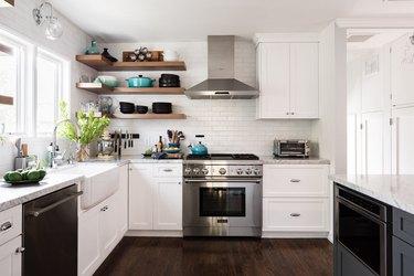 Kitchen with gas range, hood, white cabinets, farmhouse sink, window, open shelves.