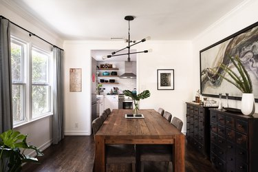 white rustic dining room with wooden table and black pendant light