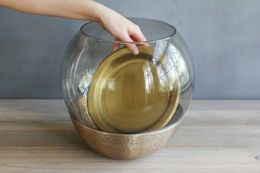placing a gold-colored paper plate to create a floor on the bottom of a glass lamp globe
