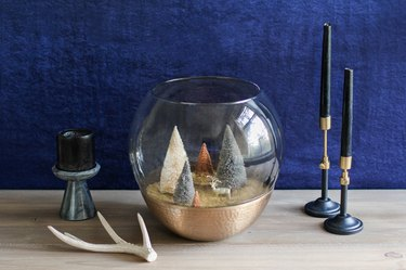 a holiday scene made from a glass lamp globe and bottle-brush trees