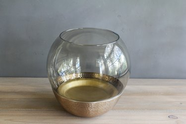 a glass lamp globe inside a copper bowl with a gold-colored paper plate at the bottom