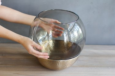 placing a glass lamp globe inside a copper bowl