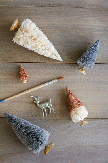 a paint brush, a deer figurine, and trees made from bottle brushes