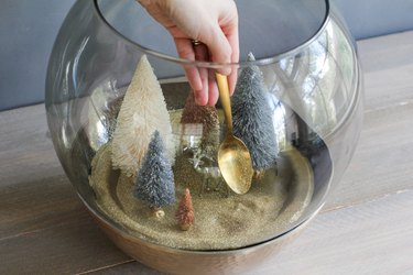 a crafter uses a gold spoon to add glitter to a holiday scene in a glass terrarium