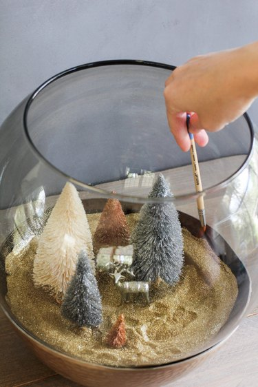 a crafter uses a paint brush to tidy up glitter inside a glass terrarium