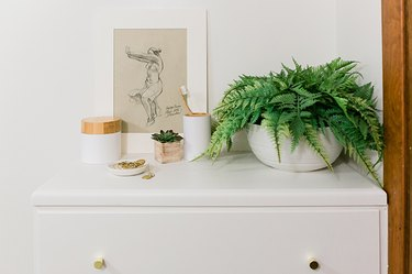small bathroom wall art with several toiletry containers on top of a dresser
