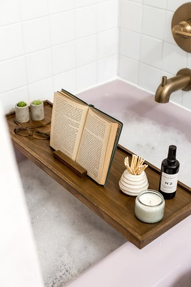 Wood bath tray with reading glasses, book, plants over bathtub