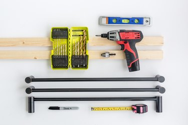 Wood boards, metal towel bars, measuring tape, power drill, level, sharpie