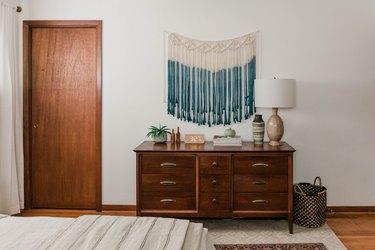 Bohemian blue and white macrame wall hanging over dresser in bedroom