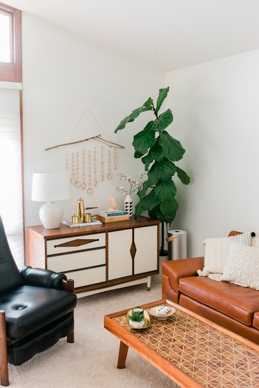 Mid-century leather and wood furniture in white-walled room with plant