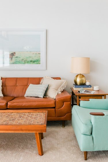 Living room with brown leather sofa, coffee table, side table, and turquoise accent chair