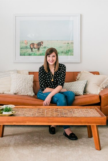 Person sitting in living room on leather couch with coffee table and art