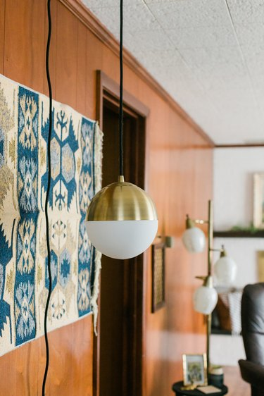 Wood wall with. blue-white tapestry and mid-century globe pendant lamps