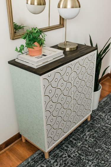 DIY entryway cabinet with plant, lamp, and books on hardwood floor with blue rug and plant against white wall with mirror