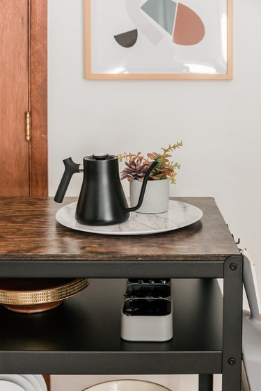 Farmhouse kitchen island with dishware and small plant on wood top